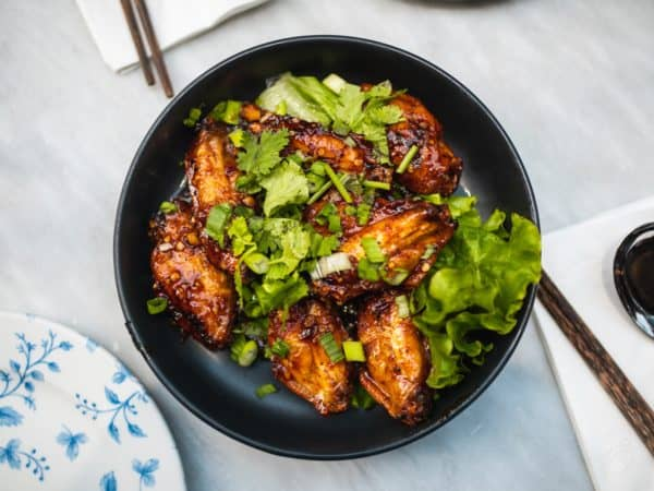 A dish of Chinese Wings with scallions, lettuce and cilantro that looks to die for